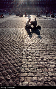 DH69HF Couple sitting on the cobblestones of the Plaza Mayor, Madrid, Spain, Europe